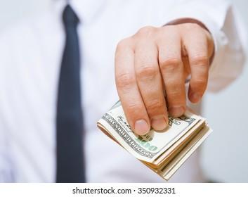 Unrecognizable businessman giving a hundred dollars, closeup shot
