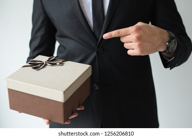Unrecognizable businessman holding brown gift box and pointing with forefinger at it. Sales manager presenting Christmas present. Holiday shopping sale concept