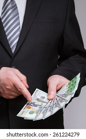 Unrecognizable businessman holding dollars and euro and choosing dollars