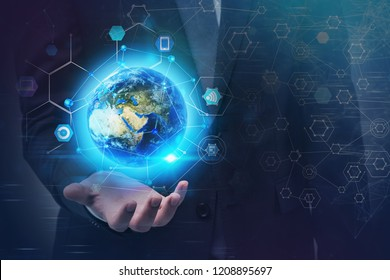 Unrecognizable businessman holding earth hologram with internet of things icons around it. Toned image double exposure Elements of this image furnished by NASA