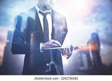 Unrecognizable businessman with laptop standing over blurred cityscape background with glowing network interface foreground. Toned image double exposure