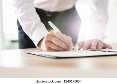Unrecognizable businessman leaning in to sign a contract on his office desk with lens flare.