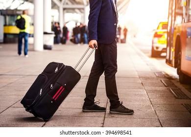 Unrecognizable businessman with luggage at the airport, entering