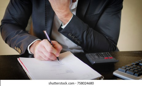 Unrecognizable businessman sitting at his desk in the office and writing on sheet of paper