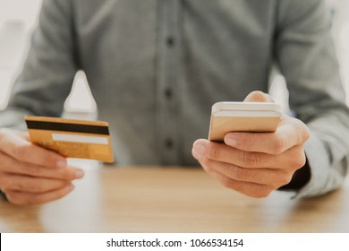 Unrecognizable businessman sitting at table, holding mobile phone and credit card and typing card data to make online payment