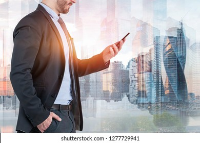 Unrecognizable businessman in suit looking at smartphone over Moscow city background. Toned image double exposure