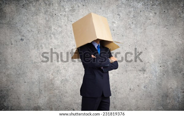 Unrecognizable businessman in suit wearing carton box on head