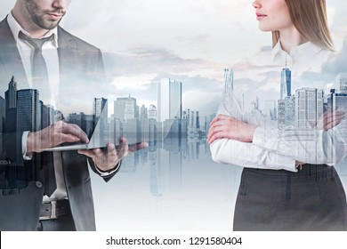Unrecognizable businessman using laptop and confident businesswoman standing with crossed arms over modern cityscape background. Concept of management. Toned image double exposure