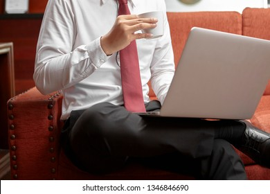 unrecognizable businessman using laptop while enjoying coffee in cafe