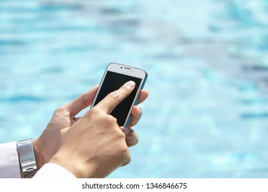 unrecognizable businessman using phone on pool side
