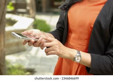 unrecognizable businesswoman using handphone in the park