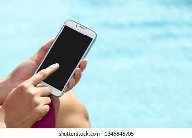 unrecognizable businesswoman using phone on pool side