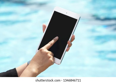 unrecognizable businesswoman using tablet on pool side
