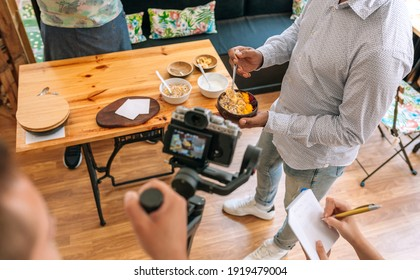 Unrecognizable camera operator recording a streaming cooking tutorial. Selective focus on breakfast bowl in background