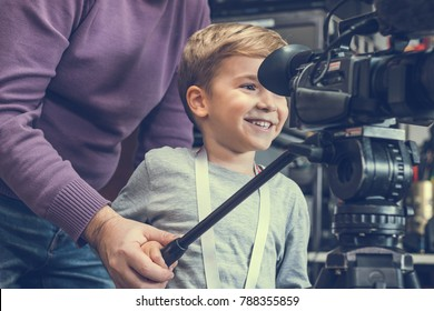 Unrecognizable cameraman teaching happy kid how to record and use video camera.