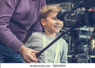 Unerkennbarer Kameramann lehrt glückliches Kind, wie man Videokamera aufnimmt und benutzt.