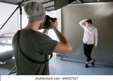 Unrecognizable casual photographer taking shots of male model in studio. Fashion photoshoot backstage