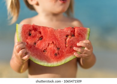 Unrecognizable caucasian little girl eat watermelon at beach