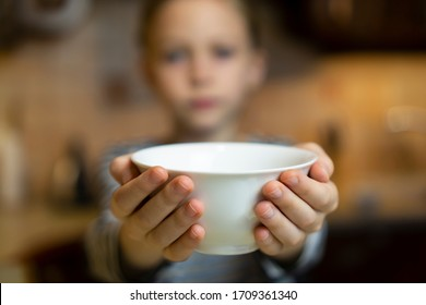 Unrecognizable child girl reaching out hands holding white empty bowl plate offering food or asking for food. Shallow focus. Giving concept. Hungry children