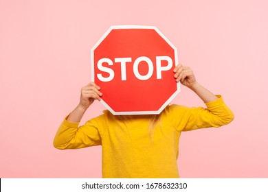 Unrecognizable child in yellow sweatshirt covering face with Stop symbol, anonymous person holding red traffic sign, warning about road safety rules. indoor studio shot isolated on blue background
