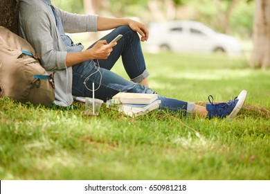 Unrecognizable college student relaxing on green lawn and listening to music in headphones, profile view