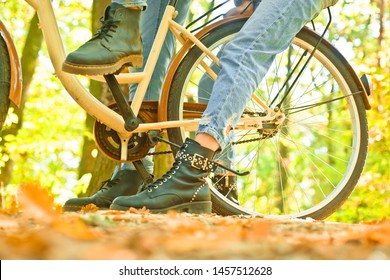 Unrecognizable couple with bike stand in autumn forest. Romantic couple on date. Date and love. Couple in love ride bicycle in forest park. Ideas for perfect autumn date. Romantic date with bicycle.