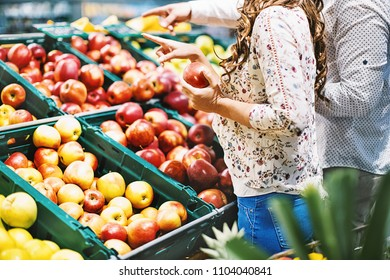 Unrecognizable couple buying fresh apples at a grocery store. Side view. Horizontal.