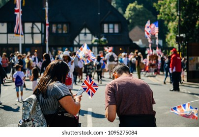 Unrecognizable couple with flags using phone on Windsor street for royal wedding marriage celebration of Prince Harry, Duke of Sussex and the Duchess of Sussex Meghan Markle