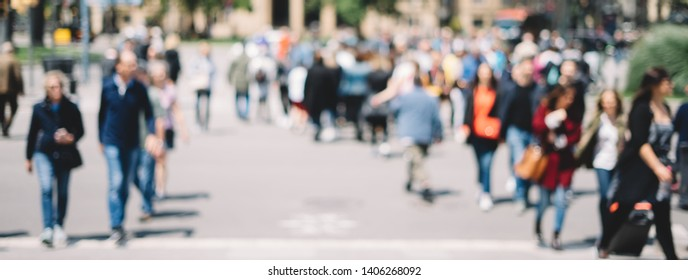 Unrecognizable crowd of people in bokeh walking in a city. Blurred image