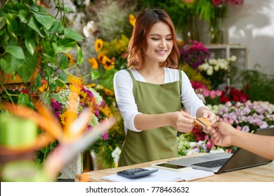 Unrecognizable customer giving credit card to pretty Asian saleswoman in order to pay for purchases, interior of flower shop on background
