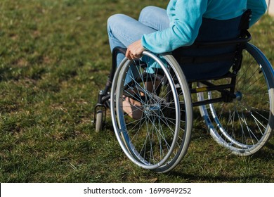 Unrecognizable disabled woman young woman in a wheelchair outdoors in a park. Recovery and healthcare concepts.