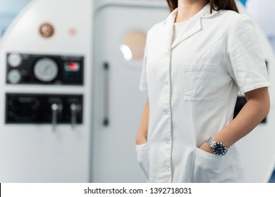 Unrecognizable doctor holding hands in pockets while standing in front of hyperbaric chamber at clinic.