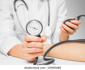 Unrecognizable doctor measures blood pressure a patient by sphygmomanometer