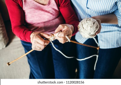 An unrecognizable elderly grandmother and adult granddaughter at home, knitting.