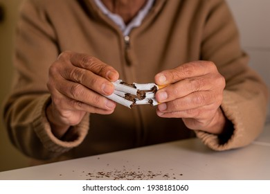 Unrecognizable elderly man, out of focus, with a handful of cigarettes in his hands, which he has split in half, rejecting tobacco.