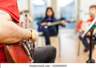 unrecognizable electric guitar teacher teaching young boys at music school