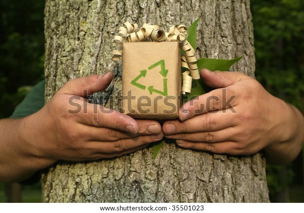 Unrecognizable Environmentalist person holding gift with recycling symbol in front of tree bark and leaf