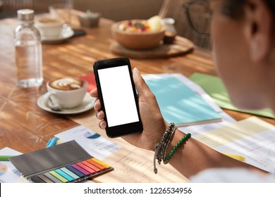 Unrecognizable ethnic young woman holds modern smart phone with blank screen, syncronizes multimedia, reads news in internet, drinks coffee, has paper documentation on desk. Copy space display