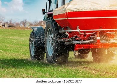 Unrecognizable farmer in agricultural tractor is fertilizing wheat crop field with NPK fertilizer nutrients