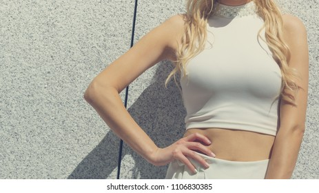 Unrecognizable fashionable woman wearing high fashion short white crop top during summer weather.