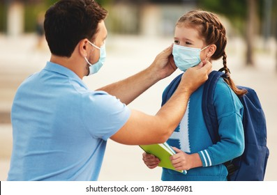 Unrecognizable father putting medical mask on face of cheerful schoolgirl while preparing for school during coronavirus pandemic