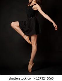 Unrecognizable female ballet dancer in black dress and pointe shoes at dark studio background