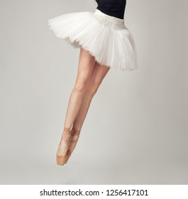 Unrecognizable female ballet dancer with tutu and pointe shoes in studio background