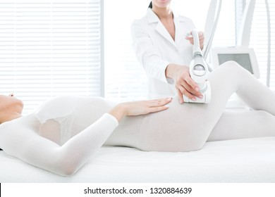 Unrecognizable female beautician in white medicine gown, attends female patient in cosmetological wellness clinic, performing LPG massage on hips in white slimming suit in white treatment room