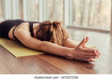Unrecognizable female with clasped hands lying on floor face down during yoga training in gym