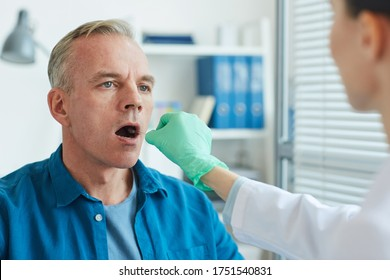 Unrecognizable female doctor taking swab sample from mouth and throat of mature man for virus test in clinic, copy space