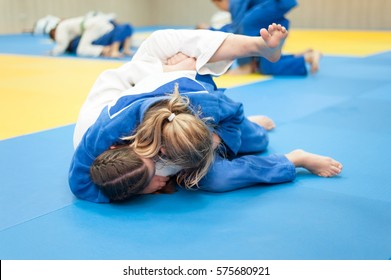 Unrecognizable female judoka in blue judo gi keeps the opponent in the hold down