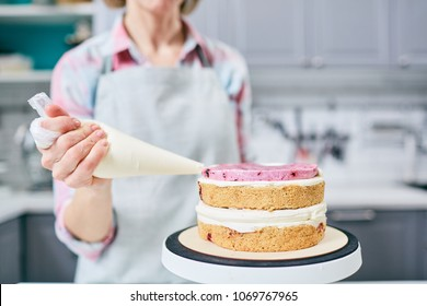 Unrecognizable female pastry cook squeezing strawberry cream on appetizing layer cake in kitchen