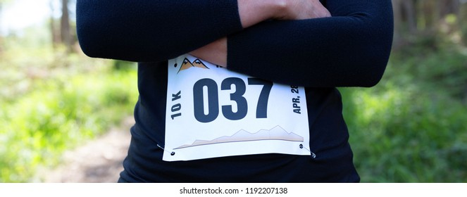 Unrecognizable female trail athlete posing with race number placed outdoors