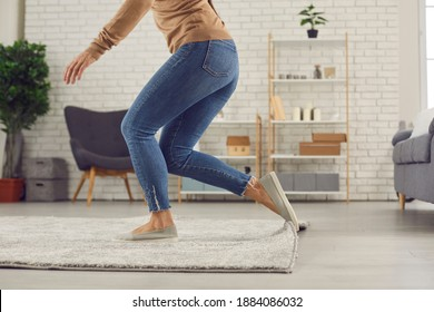 Unrecognizable female trips over rug. Clumsy faceless woman in uncomfortable shoes stumbles on rug in living-room and is about to fall on floor. Domestic accidents and getting injured at home concept - Shutterstock ID 1884086032